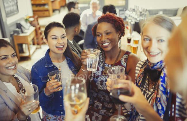 Mulheres amigas brindando vinho e copos de cerveja no bar — Fotografia de Stock