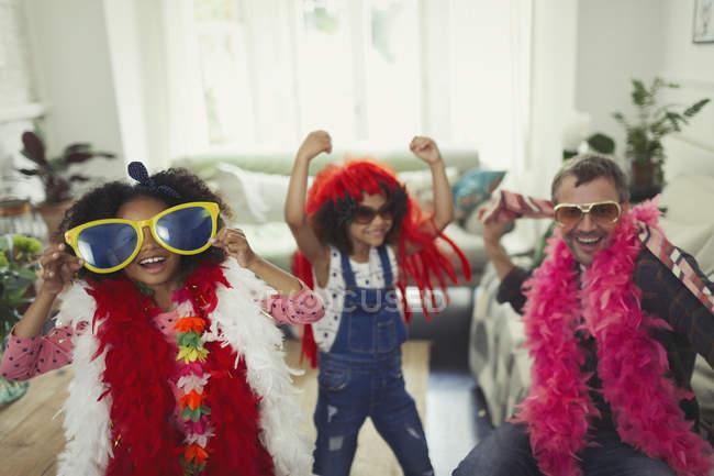 Игривый многоэтнический отец и дочери, играющие в негабаритные солнцезащитные очки и перья, играют в костюмы — стоковое фото