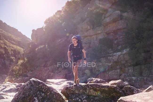 Giovane con lo zaino escursionismo sopra rocce assolate — Foto stock