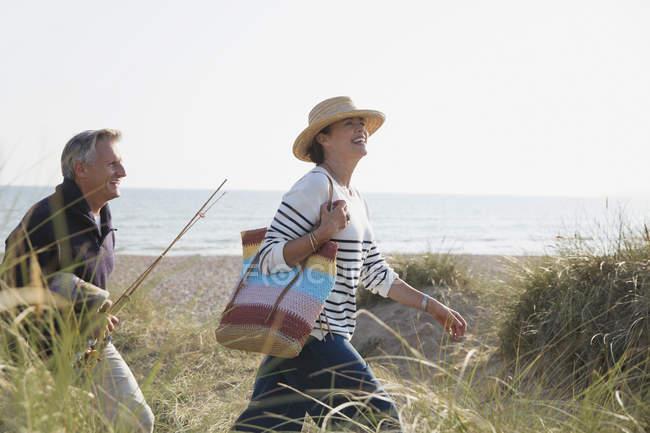 Coppia matura con canna da pesca passeggiando nell'erba soleggiata della spiaggia — Foto stock
