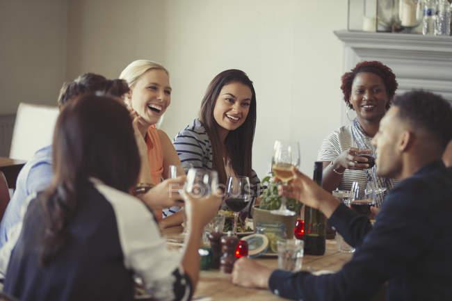 Amigos bebendo vinho e conversando na mesa do restaurante — Fotografia de Stock