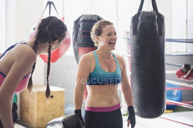 Laughing female boxers next to punching bags in gym — Stock Photo