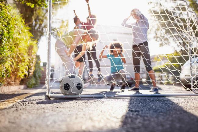 Друзі, які грали у футбол на сонячних літніх міських вулиць — стокове фото