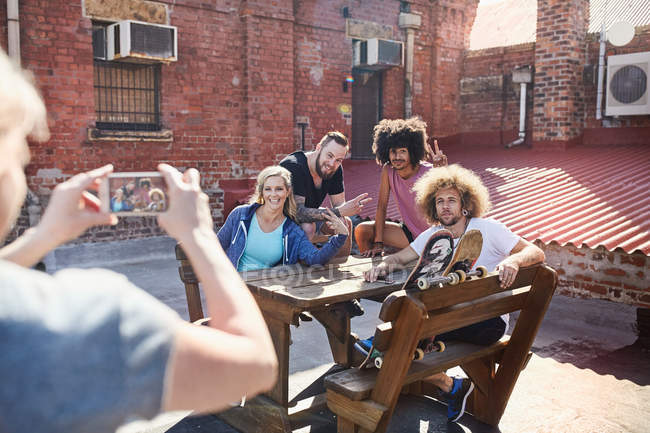 Woman with camera phone photographing friends hanging out on sunny urban rooftop — Stock Photo