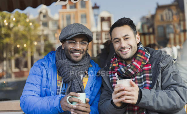Portrait smiling young men friends in warm clothing drinking coffee at urban sidewalk cafe — Stock Photo