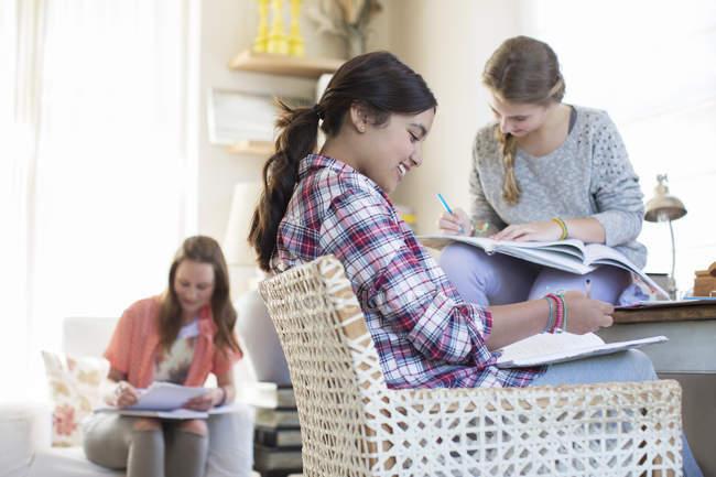 Trois jeunes filles à faire leurs devoirs dans la salle — Photo de stock