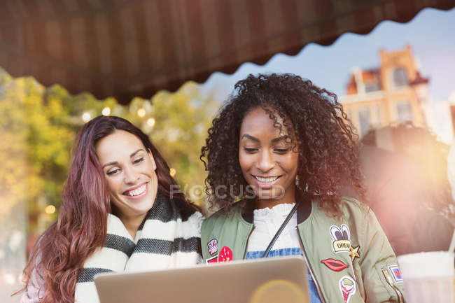 Lächelnde junge Freundinnen mit Laptop am Straßencafé — Stockfoto
