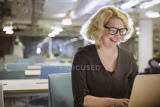 Smiling businesswoman working late at laptop in dark office — Stock Photo