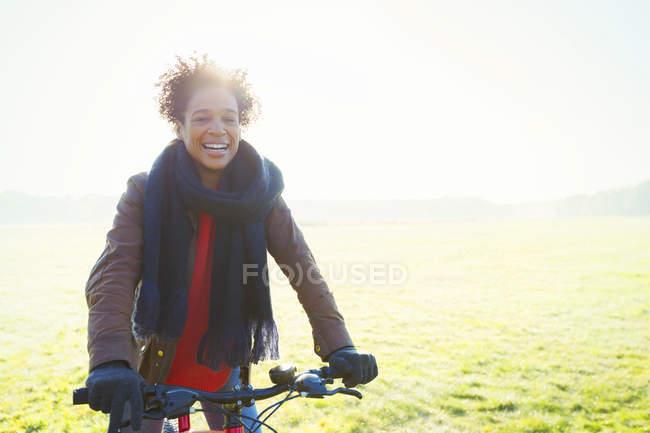 Усміхнене жінка їзда на велосипеді в траві Сонячний парк — стокове фото