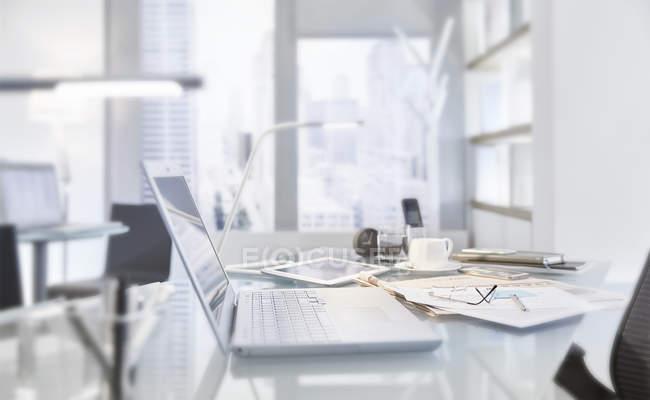 Tavolo disordinato in sala conferenze di ufficio moderno con computer portatile — Foto stock
