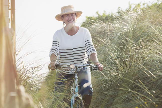 Lächelnde ältere Frau radelt am Strandgras entlang — Stockfoto