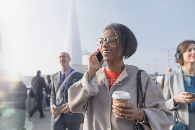 Smiling businesswoman drinking coffee and talking on cell phone on sunny busy urban pedestrian bridge — Stock Photo