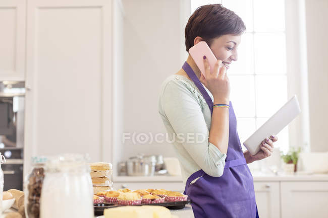 Female caterer baking, talking on cell phone and using digital tablet in kitchen — Stock Photo