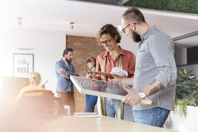 Smiling design professionals reviewing storyboard in office — Stock Photo