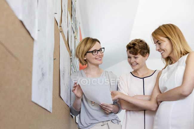 Designer femminili sorridenti che rivedono le prove alla bacheca in ufficio — Foto stock