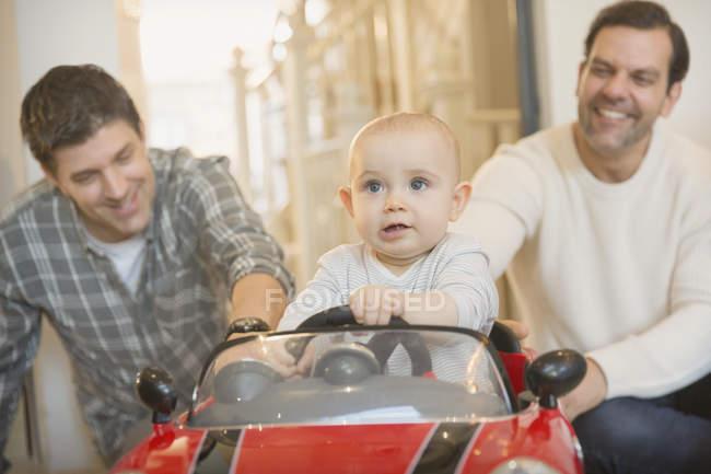 Masculino gay pais empurrando bebê filho no brinquedo carro — Fotografia de Stock