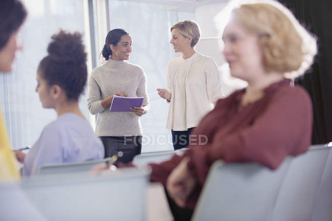 Jeunes femmes d'affaires parlant dans le public de la conférence — Photo de stock