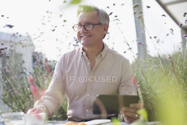 Smiling senior man using digital tablet on sunny patio — Stock Photo