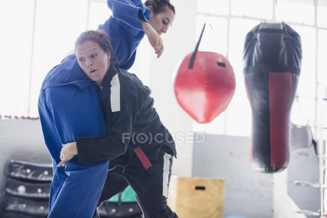 Entschlossenen Frauen üben Judo in Turnhalle — Stockfoto