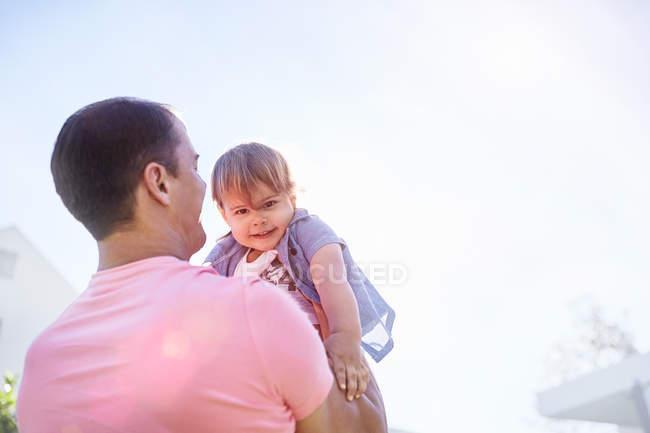 Отец сына подъема ребенка вне — стоковое фото