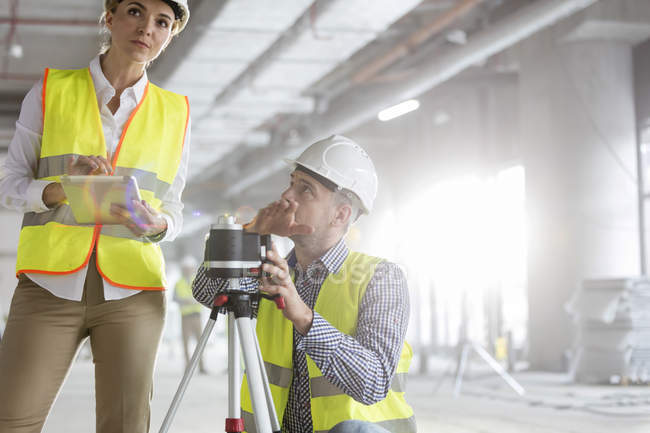Engineers with digital tablet and theodolite surveying construction site — Stock Photo