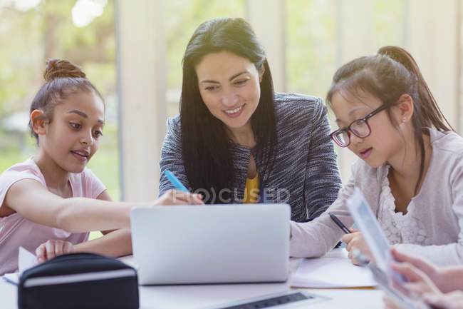 Female teacher and girl students researching at laptop in library — Stock Photo