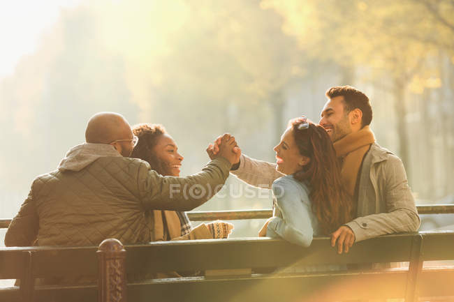Friends laughing, hanging out on autumn bench — Stock Photo