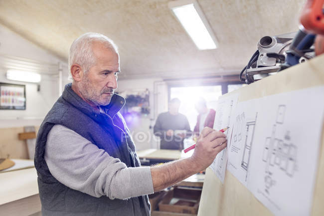Senior male carpenter editing plans in workshop — Stock Photo