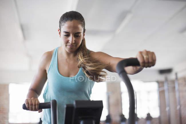 Сосредоточенная молодая женщина с тренером по эллипсу в спортзале — стоковое фото