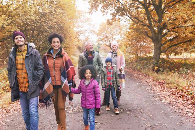 Multi-generation family walking on path in autumn park — Stock Photo
