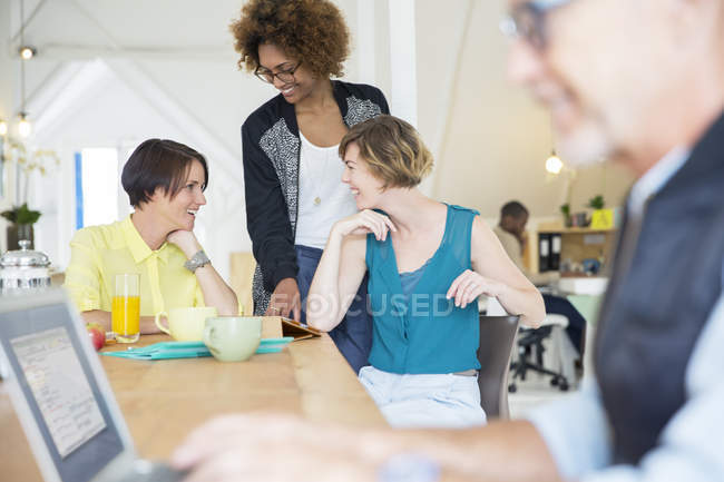 Smiling office workers talking at desk during break — Stock Photo
