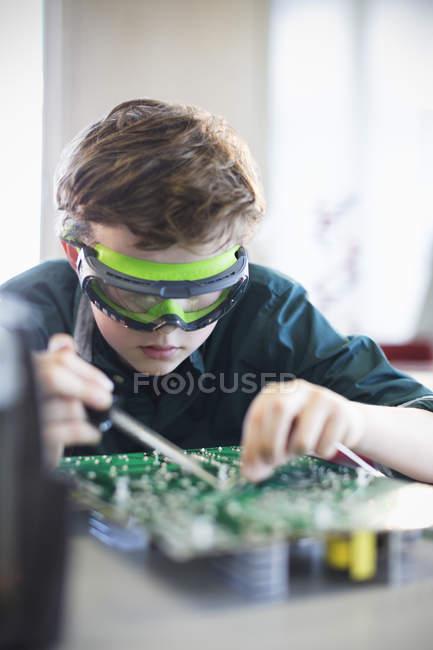 Цілеспрямований хлопчик студента в окуляри, Пайка друкованій платі в класі — стокове фото