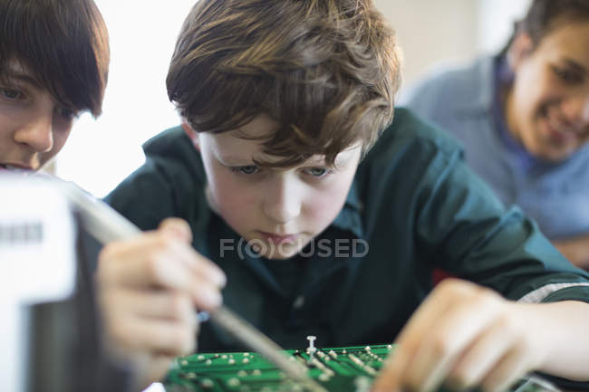 Focused boy student assembling electronics in classroom — Stock Photo