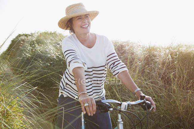 Lächelnde ältere Frau radelt auf sonnigem Strandgrasweg — Stockfoto