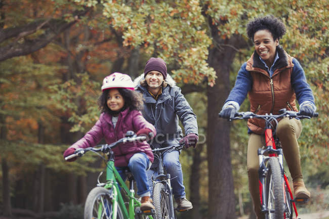 Playful young family bike riding in autumn park — Stock Photo