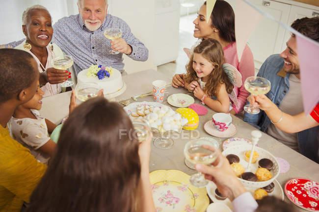 Multi-étnico multi-generación de tostadas familiares con champán en la mesa - foto de stock