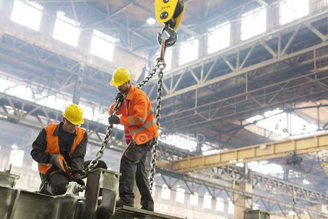 Сталевары крепят цепь крана к стали на заводе — стоковое фото