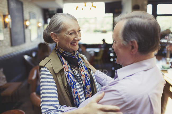 Affectionate senior couple hugging in bar — Stock Photo