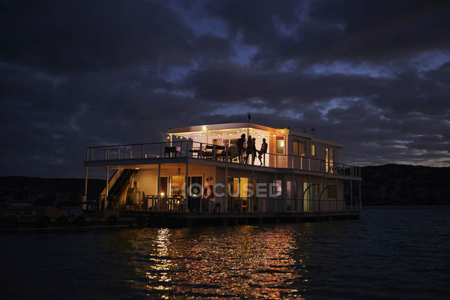 Літній houseboat висвітлюватися на ніч океану — стокове фото