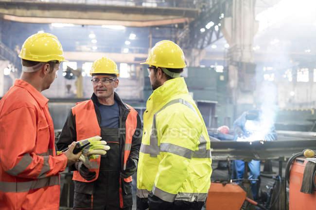 Чоловічий сталеві працівників говорити заводі — стокове фото