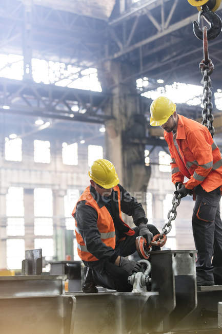 Steel workers fastening crane chain to steel in factory — Stock Photo