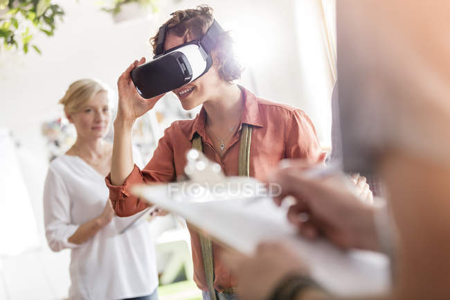 Woman using virtual reality simulator glasses in office — Stock Photo