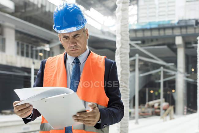 Бізнесмен рецензування документів буфер обміну на будівельному майданчику — стокове фото