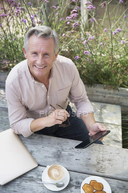 Portrait smiling senior man using digital tablet and drinking coffee at patio table — Stock Photo