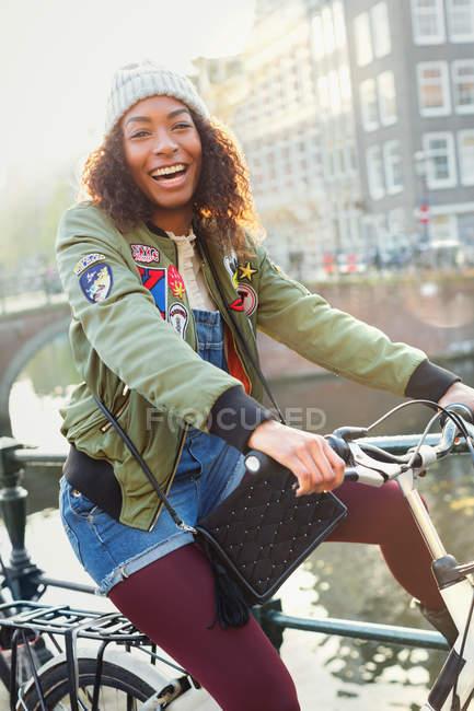 Portrait jeune femme ludique à vélo le long du canal urbain — Photo de stock