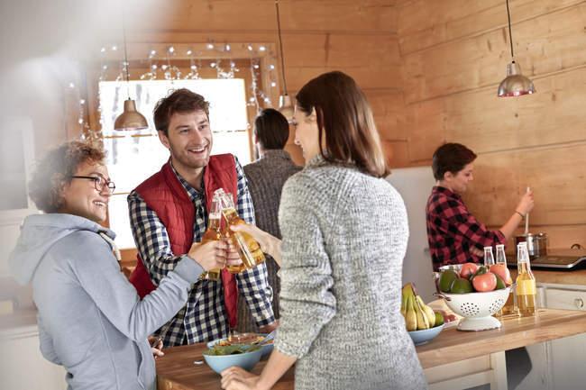 Freunde stoßen in Hüttenküche auf Bierflaschen an — Stockfoto