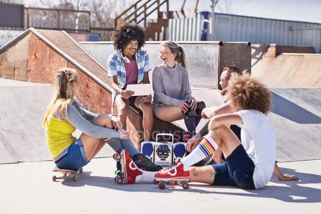 Friends in roller skates and on skateboard using digital tablet at sunny skate park — Stock Photo
