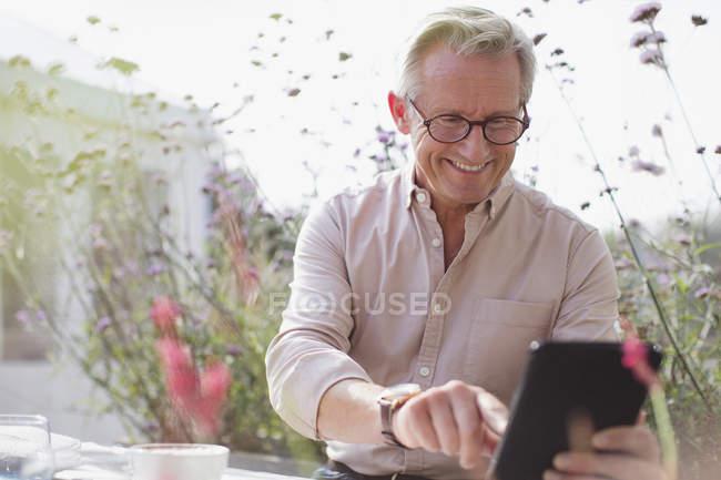 Smiling senior man using digital tablet on patio — Stock Photo