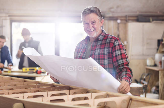 Portrait smiling male carpenter reviewing plans at wood boat in workshop — Stock Photo