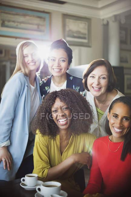 Portrait smiling women friends drinking coffee in restaurant — Stock Photo